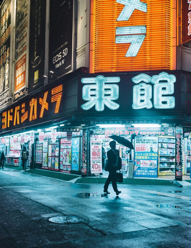 Man With Umbrella Framed By The Neon Tapestry Of Tokyo