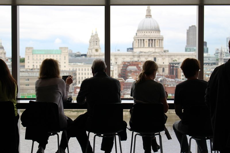 Man in Between of Four Women Sits While Watching on Window