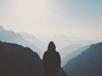 Man in Hoodie Standing in Front of the Mountain