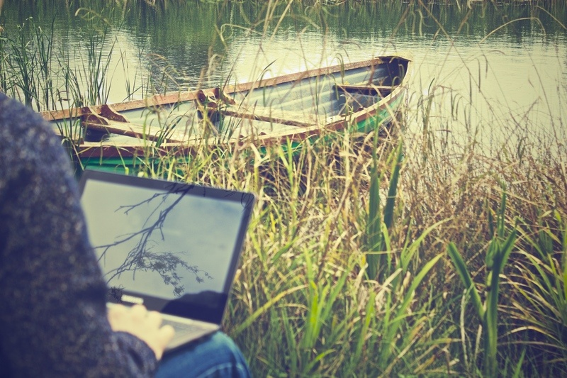 Man on Laptop with Boat