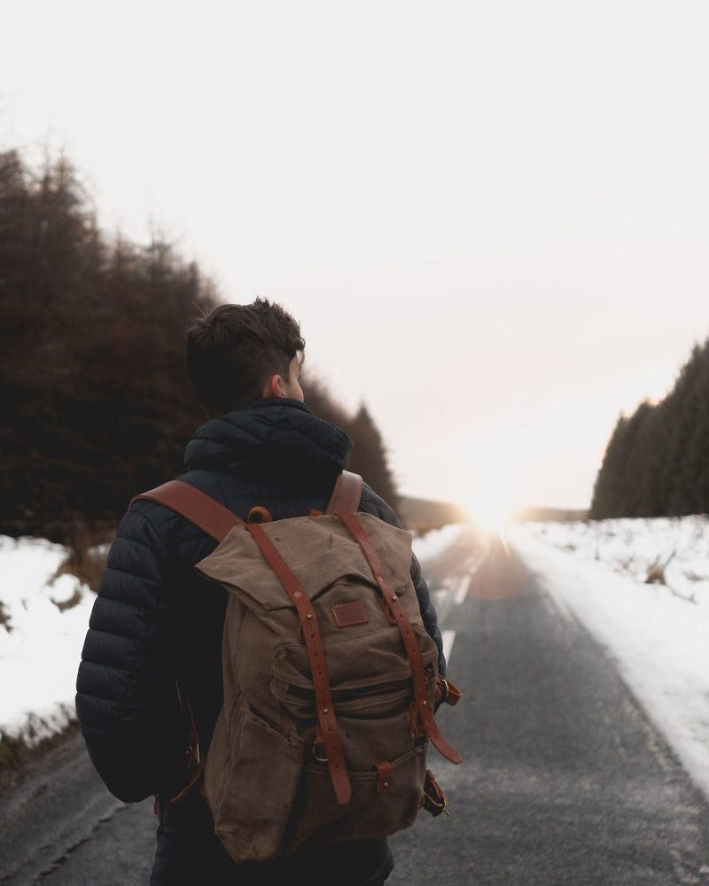 Man with Backpack Standing in Middle of Road