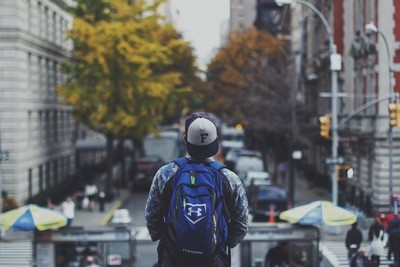 Man with Backpack on Street in Shallow Focus