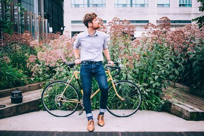 Men's Fashion Man In Shirt And Jeans Leaning On Bicycle