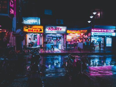 Neon Shop Lights Reflect On Rain-Wet Streets In India