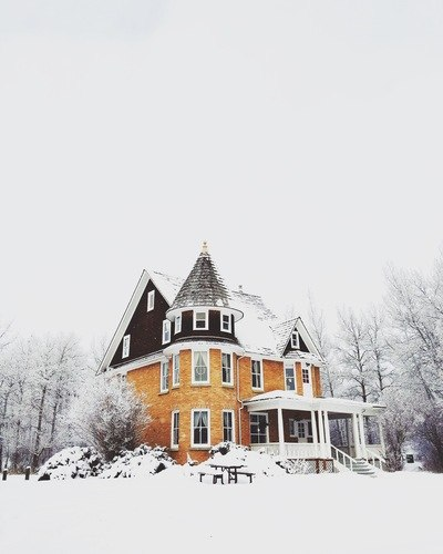Orange And Gray Concrete House Surround By Snow
