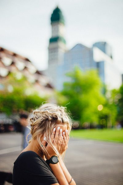 Person Covering Face with Hands Outdoors