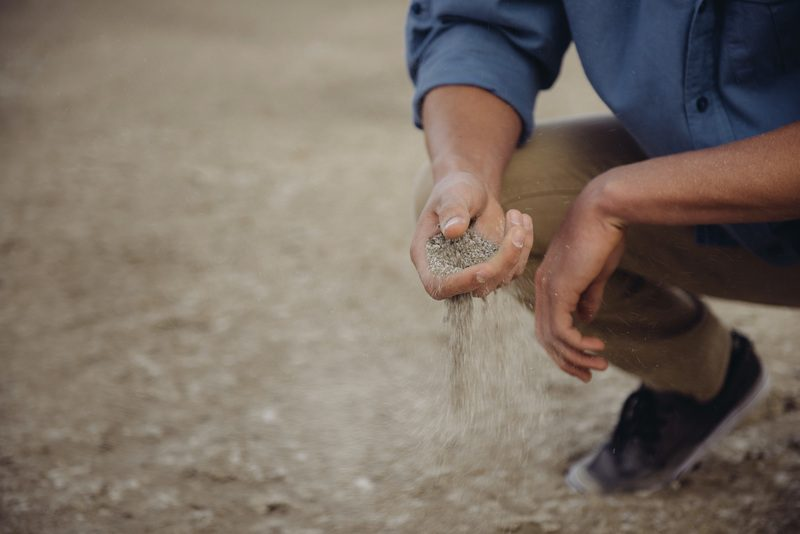 Person Crouches Down with A Handful of Sand That Slips Through