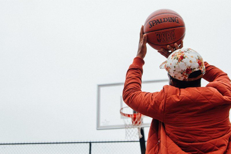 Person Holding Basketball Looking At Basketball Hoop System