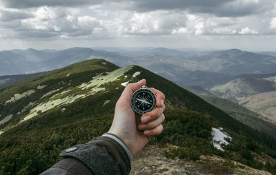 Person Holding Silver Compass