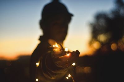 Person Holding String Lights At Nightitme