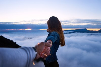 Person Holding Woman's Hand on Top of Hill