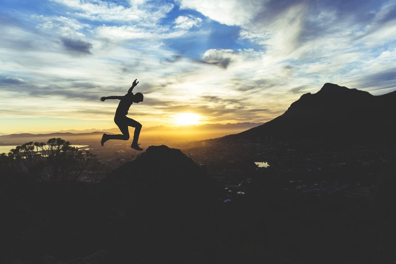 Person Jumping on Hill at Sunset