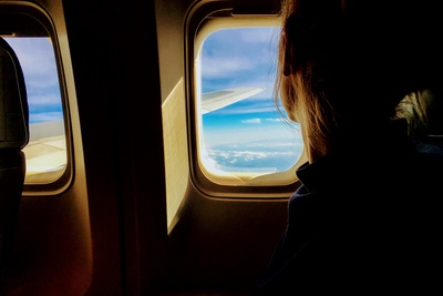 Person Looking Outside of Airplane Window