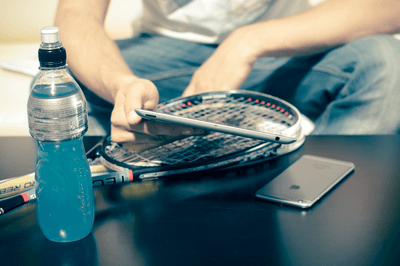 Person Sitting While Using Iphone 8 And Tennis Racket Beside Energy