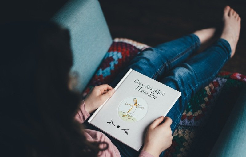 Person Sitting on Chair Reading Book