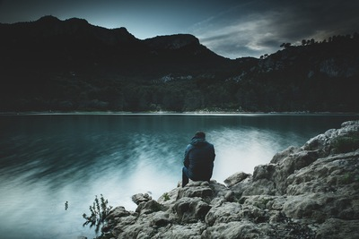 Person Sitting on Rock Near Water
