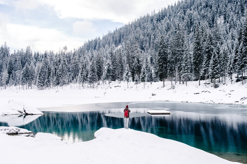 Person Standing Beside Water Surrounded By Snow Field Near