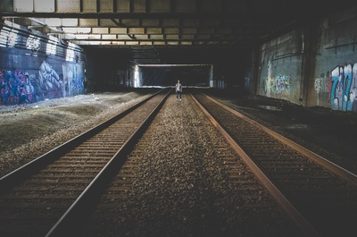 Person Standing in the Middle of Train Rail Tracks