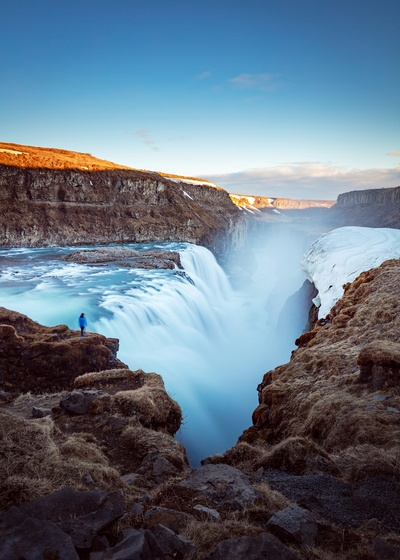 Person Standing on Cliff Near Large Waterfalls  At