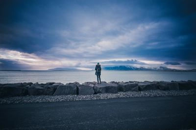 Person Standing on Rock Looking Sea