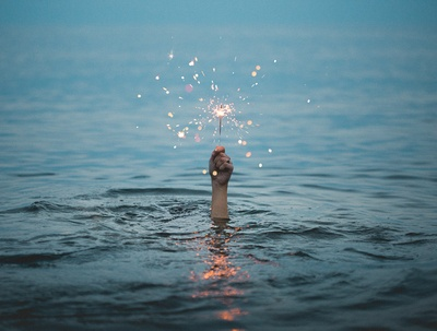 Person Submerged in Water Holding Sparkler