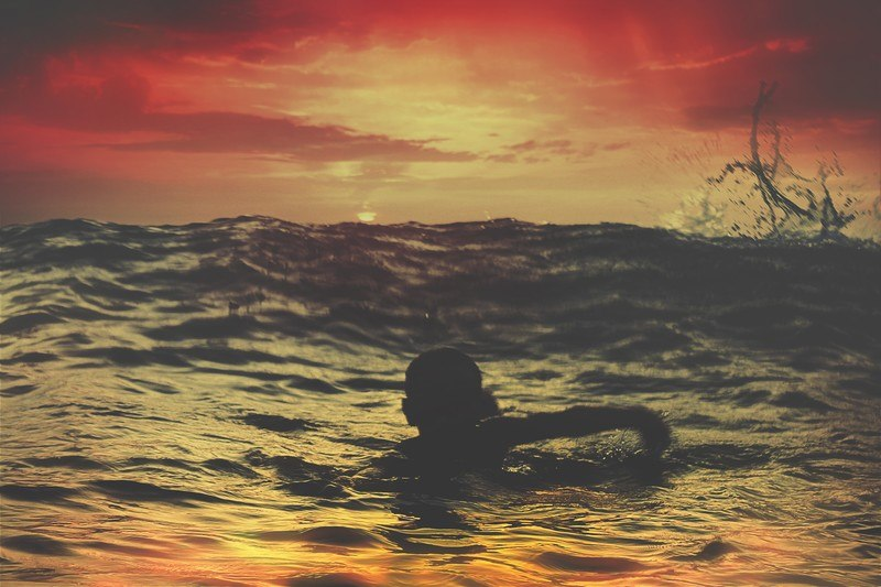 Person Swimming in Water Under Red And Orange Sky