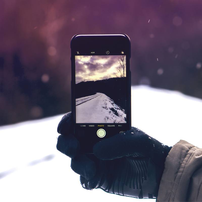 Person Taking Photo on Snowy Field
