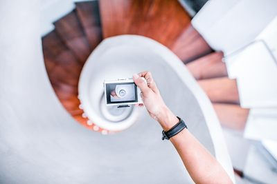 Person Taking Picture of White Spiral Staircase
