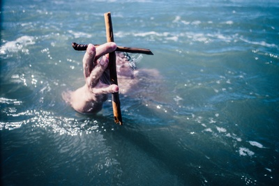 Person Under Water Holding Brown Wooden Cross Above Water