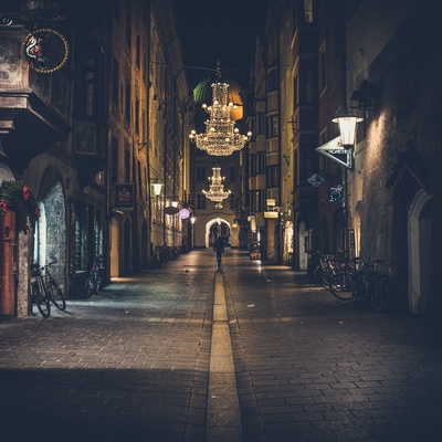 Person Walking on Pathway Showing Lighted Chandelier at Night Time