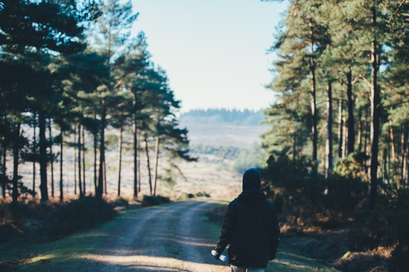 Person Wearing Jacket Walking on Dirt Road