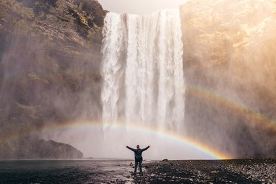 Person in Front of Waterfalls with Double Rainbow