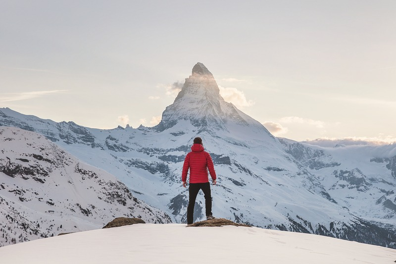 Person in Red Hoodie Standing on Snowy Mountain