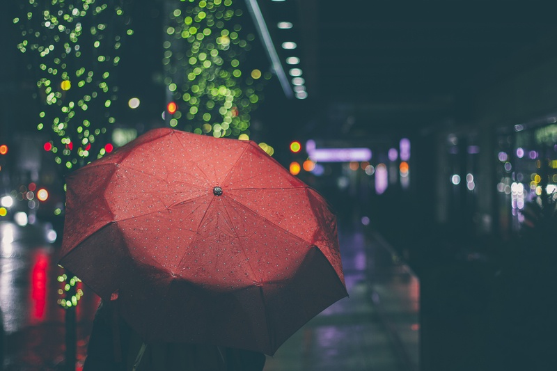 Person with Red Umbrella Walking on Street at Nighttime