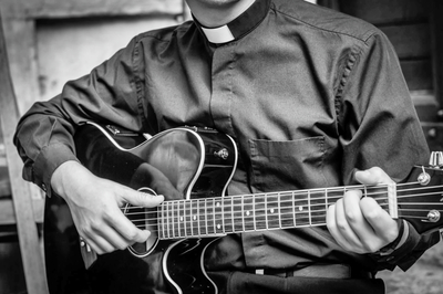 Priest playing the guitar