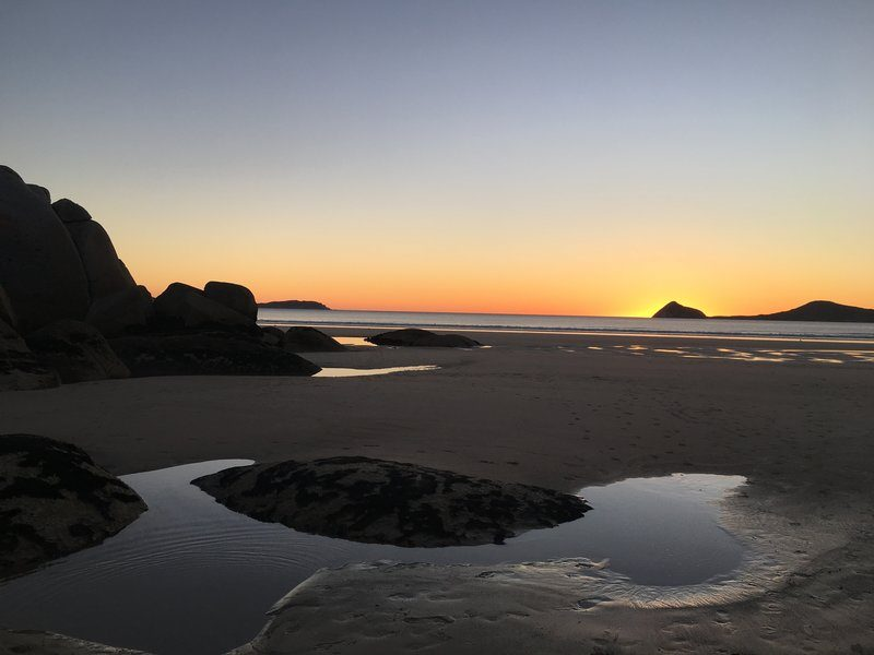 Puddles Of Water On the Beach Reflect The Sunset