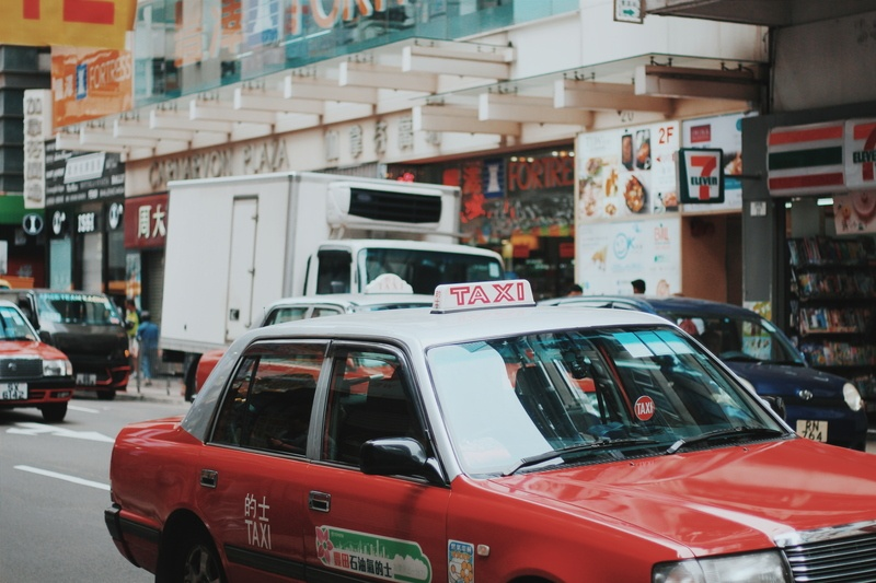 Red And White Taxi Sedan Running on Road Near 7 Eleven