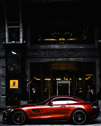 Red Coupe Parked in Front of Black And Gray Building During