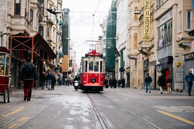 Red Tram Near Between Buildings with Person Walking