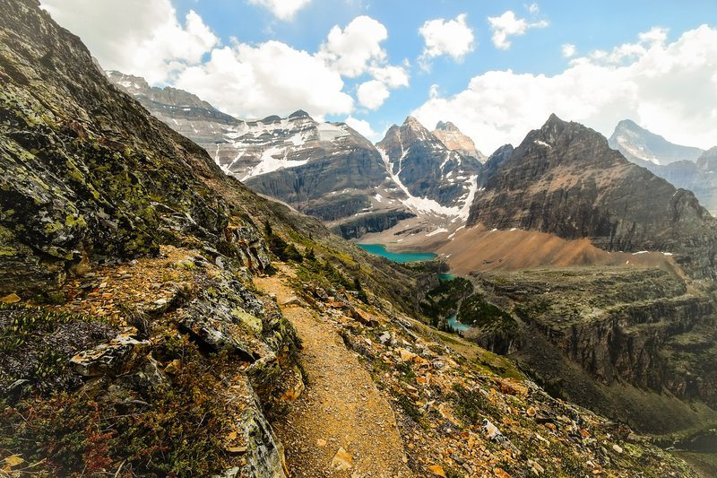 Rocky Mountain Path Leading To A Lake In A Valley