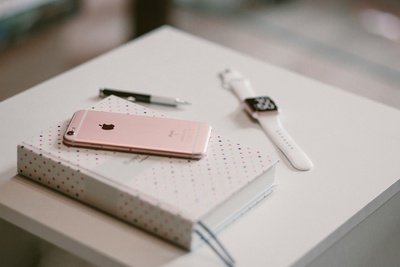 Rose Gold Iphone 6S on Book Near Apple Watch