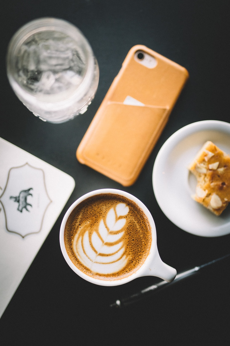 Selective Focus  Cup of Cappuccino Beside Smartphone, Saucer, And