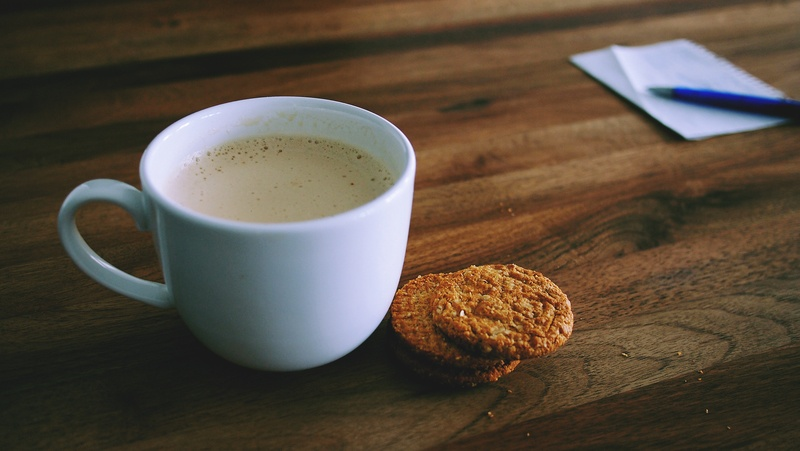 Shallow Focus Photography of White Ceramic Mug Beside Two Baked Cookies
