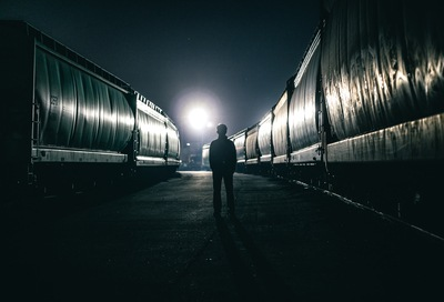 Silhouette of Man Standing Beside Train
