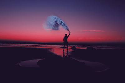 Silhouette of Man Standing on Seashore Holding Smoke Can