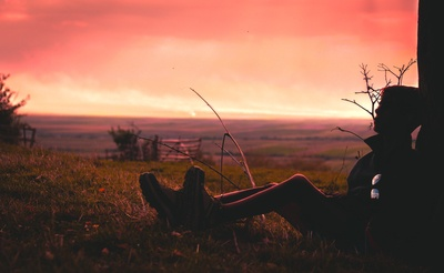 Silhouette of Person Sitting on Green Grass