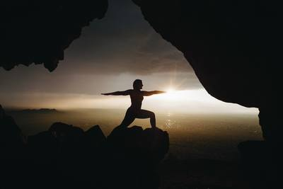 Silhouette of Person in Yoga Post on Top of Cliff During