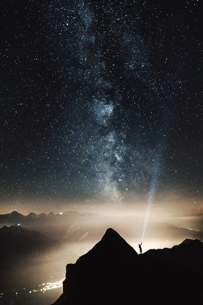 Silhouette of Person on Top of Mountain Pointing Flashlight on Sky