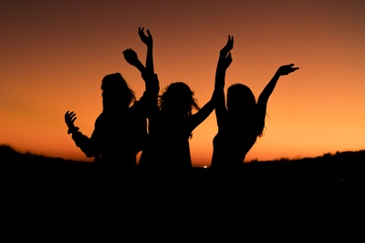 Silhouette of Three Woman with Hands on the Air While Dancing