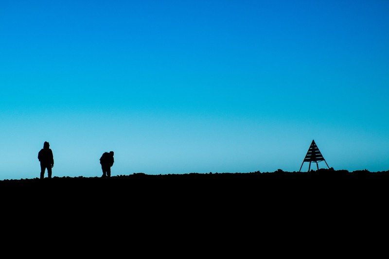 Silhouette of Two People Standing on Ground Near Tent